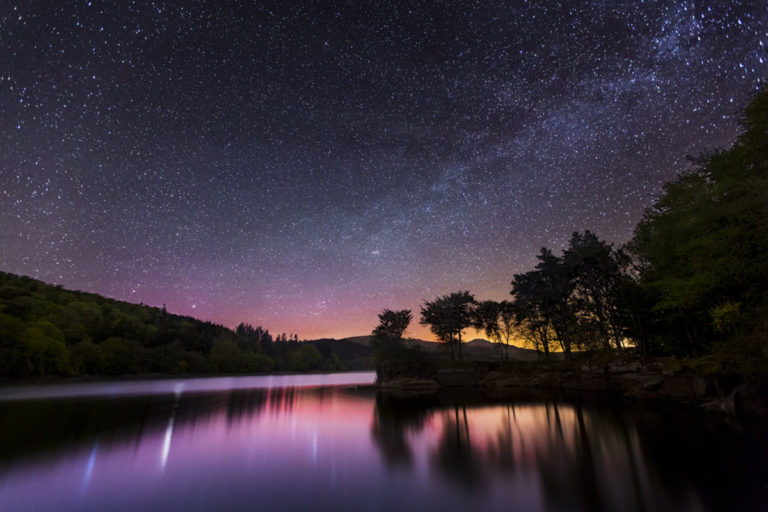 This photograph was taken at Burrator Reservoir in Dartmoor National Park. The picture was captured at night and shows the Milkyway and starry sky over the calm reservoir water. Dartmoor is a popular tourist destination as well as one of the best locations in the country for stargazing.