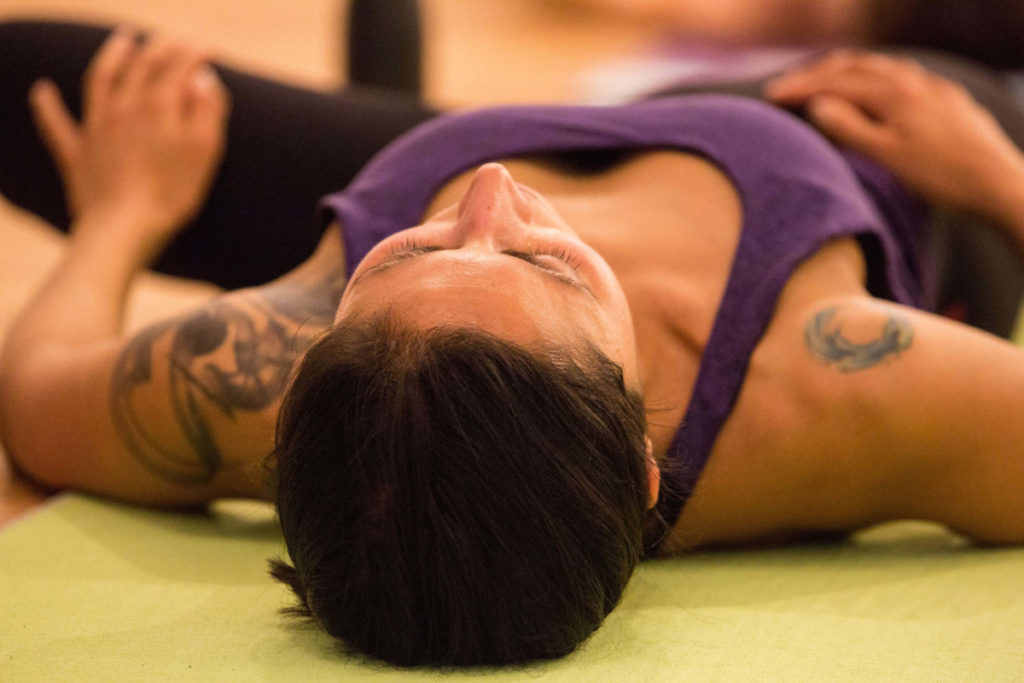 woman laying down stretching, yoga for mindfulness