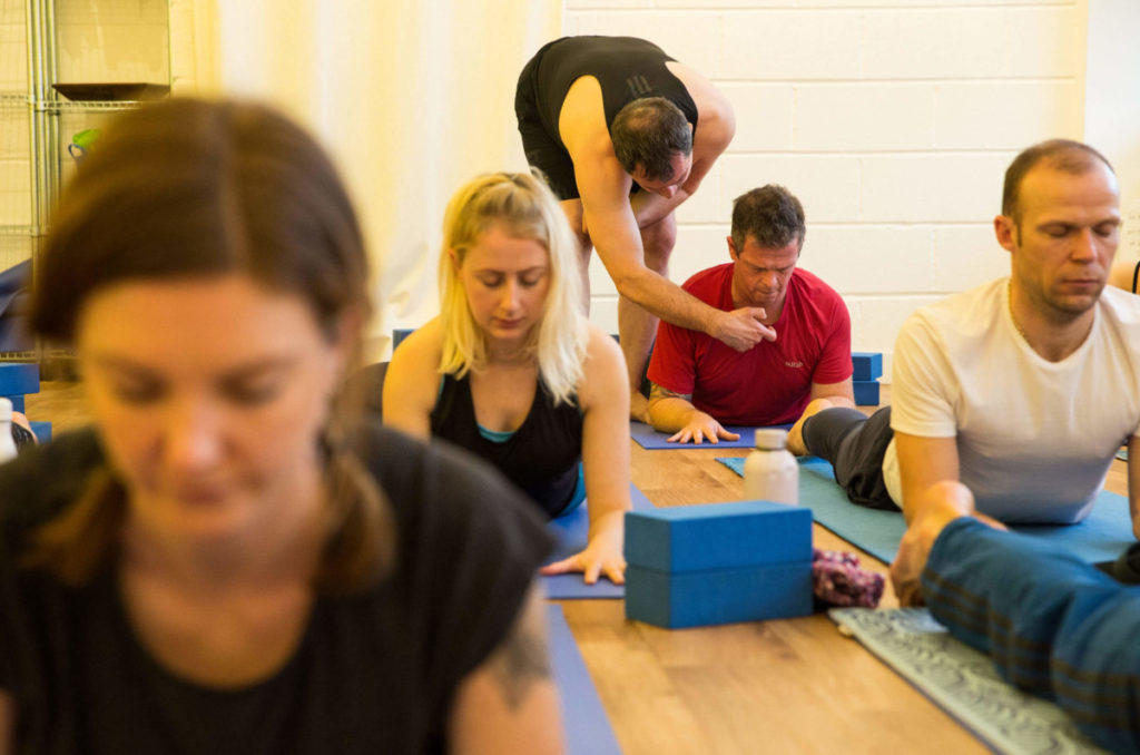 ed lead instructor assisting yoga student