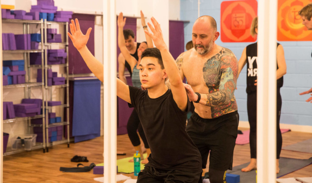 james adjusting standing chair pose in teacher training