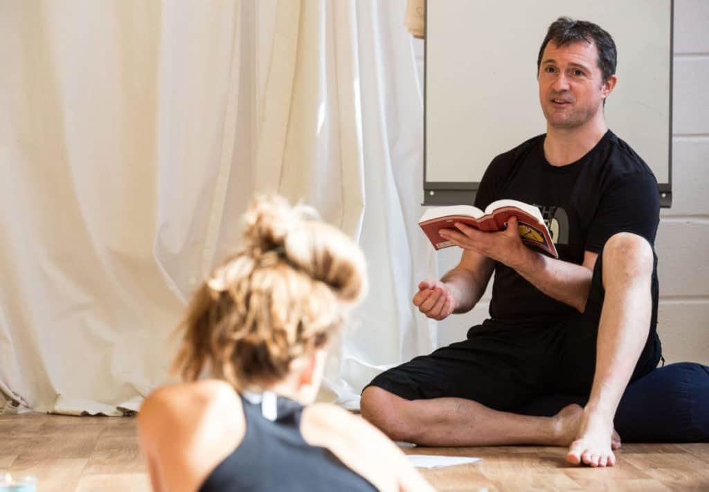 Yoga book club, man reading from Hatha Yoga Pradipika