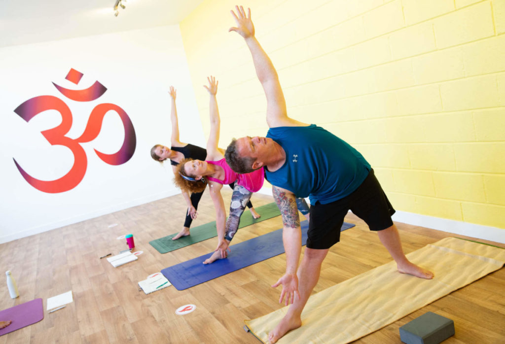 yoga teacher training course leading to teaching yoga classes, people stretching in yoga studio in Bristol