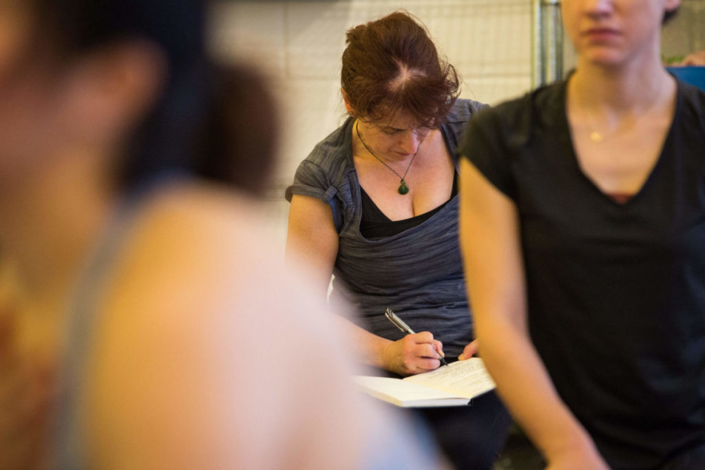 woman writing, yoga is good for maintaining positivity and metal well-being