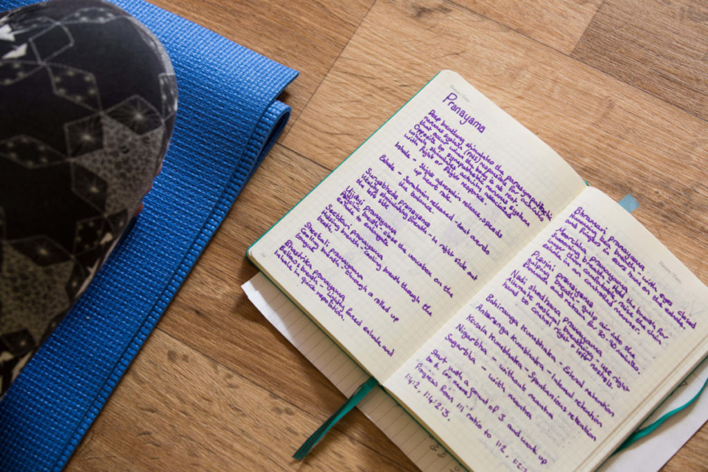 a notebook with notes from yoga teacher training sessions
