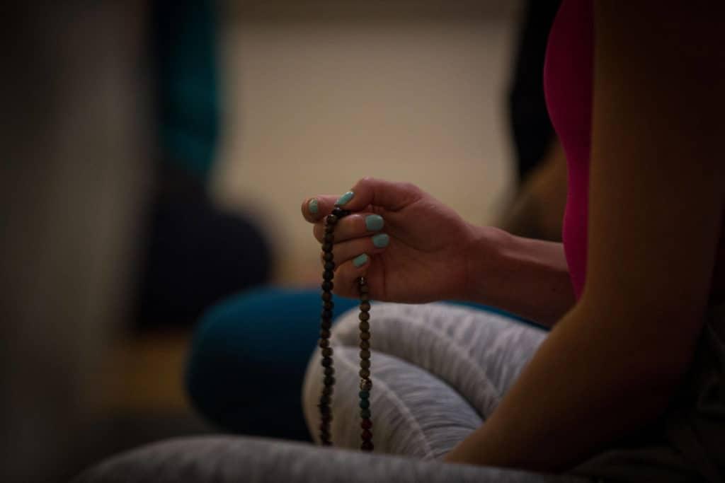 Trainee holding beads, cross-legged.