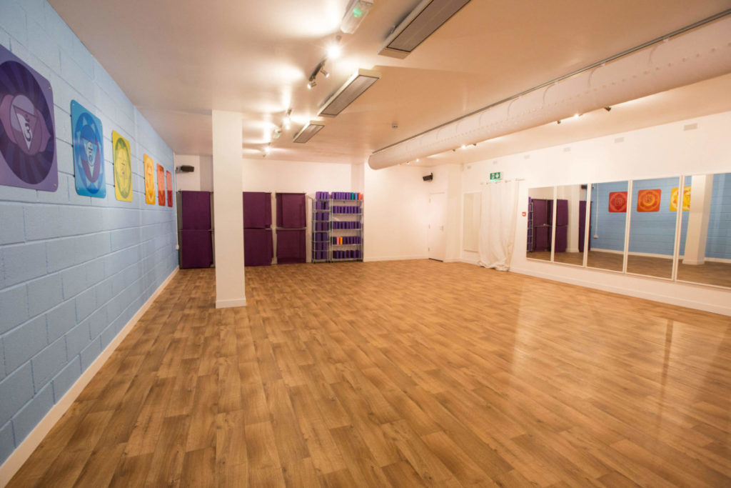 New studio with mirrors, mats and blocks on the wall.