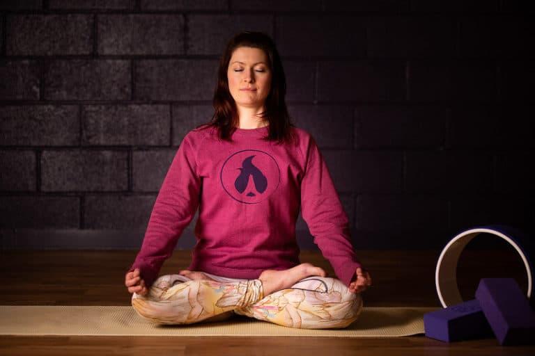 young woman doing Yoga meditation to boost serotonin levels