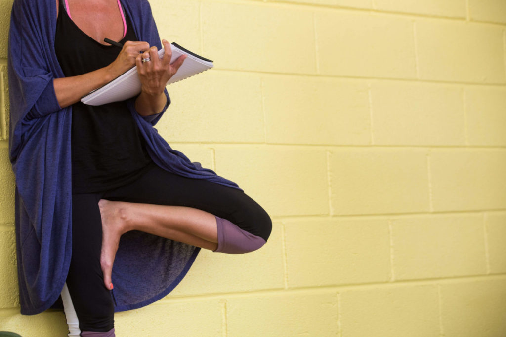 A Yoga Teacher Trainee taking notes at Yogafurie Academy in Bristol