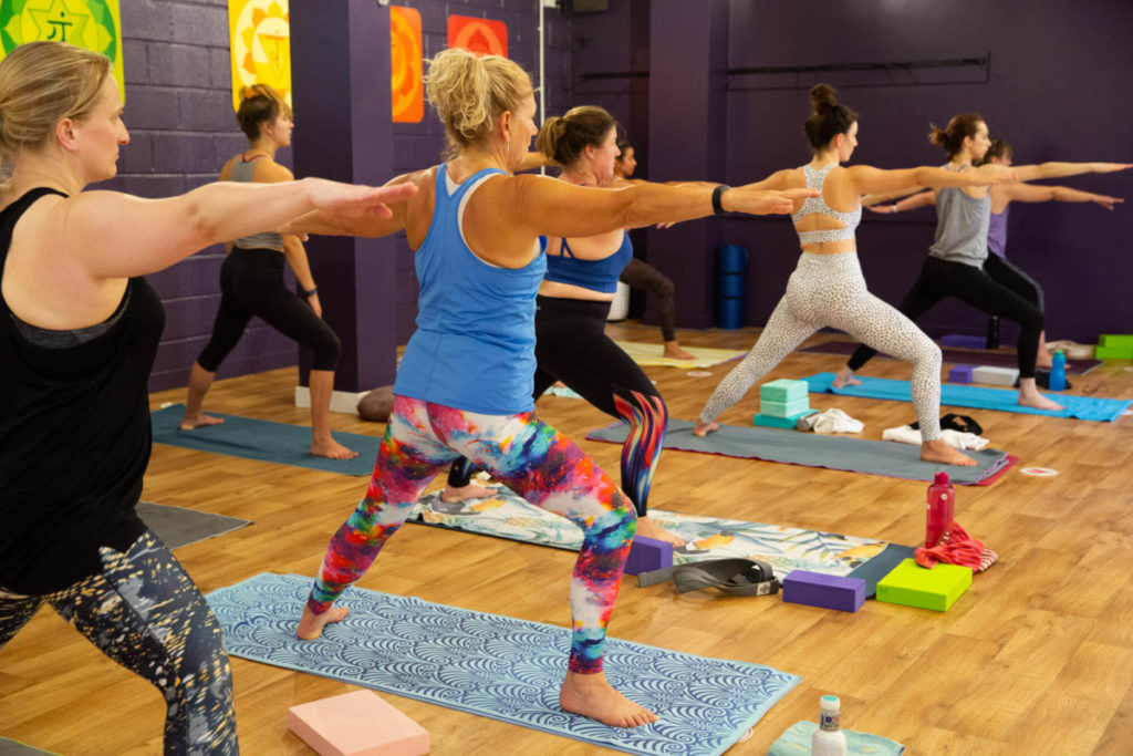 Students in Warrior 2 Pose While Studying Yoga Teacher Training in Bristol