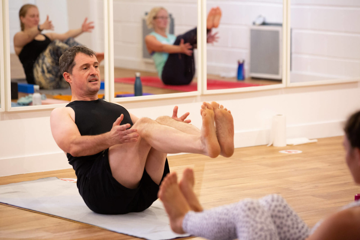 Yoga Teacher teaches Boat Pose at a Yoga Teacher Training in Bristol